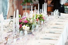 Catering table set with flowers. Catering table set service with silverware, fresh flowers and glass at restaurant before party Stock Images