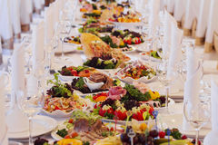 Catering table set service with silverware and glass stemware at Royalty Free Stock Images