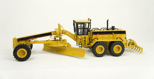Caterpillar 24h motor grader model. On a white background, with shadow royalty free stock photo
