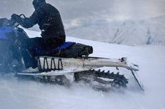 Caterpillar de la moto de nieve monta en las montañas, vista posterior Fotos de archivo