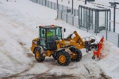 Caterpillar drehen Lader mit einem Schneepflug, der Schnee während eines Blizzards pflügt Lizenzfreie Stockfotografie