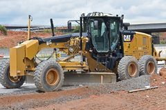 Caterpillar motor grader sits idle. A Caterpillar motor grader sits idle on a construction site after heavy rain stopped construction for a few days royalty free stock photo