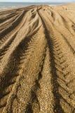 Caterpillar spår från grävaren på den steniga stranden Arkivbild