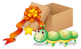 A caterpillar toy beside a box Royalty Free Stock Images