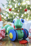 Caterpillar Toy In Front Of Christmas Tree Stock Images