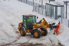 Caterpillar wheel loader with a snowplow plowing snow during a blizzard Royalty Free Stock Photography