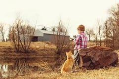 男孩和猫去catfishing在池塘 免版税库存图片