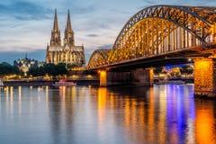 Cathédrale de Cologne et pont de Hohenzollern la nuit, Allemagne Photographie stock libre de droits
