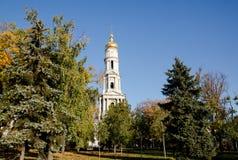 Cathédrale de l'hypothèse à Kharkov, entourée par des arbres sur le fond d'un ciel sans nuages Photos libres de droits