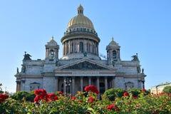 Cathédrale de St Isaac sur un fond des roses rouges le jour ensoleillé lumineux carré sous le ciel bleu Image stock