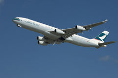 Cathay Pacific Airbus. A Cathay Pacific A340 Airbus in flight, set against azure blue sky Royalty Free Stock Images