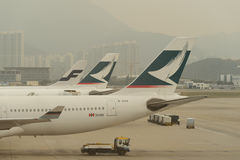 Cathay Pacific aircraft near boarding bridge Stock Photos