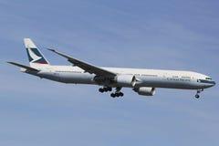 Cathay Pacific Boeing 777 en ciel de New York avant le débarquement à l'aéroport de JFK Images stock