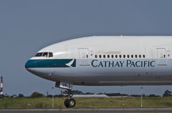 Cathay Pacific Plane Runway. A Cathay Pacific aircraft on the runway at Sydney Airport. Port Botany is visible in the background. Heat from the runway and Stock Photos