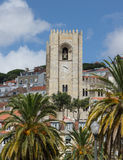 Cathedral belltower against clouds and the sky to Lisbon, Portugal Stock Photo