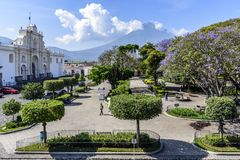 Cathedral, central park & Agua volcano, Antigua, Guatemala. Antigua, Guatemala - April 10, 2019: San José cathedral overlooks central park with Agua volcano stock photos