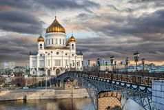 The Cathedral of Christ the Savior under dark clouds. The Cathedral of Christ the Savior and the Patriarchal Bridge in the background of dark clouds over Moscow Royalty Free Stock Images