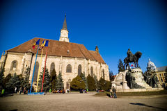 Cathedral in Cluj. A view of a cathedral and statue located in Cluj City, Romania. There are several flags flown outside the building Royalty Free Stock Images