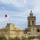 Cathedral and flag of Malta. Victoria also known among the native Maltese as Rabat on island Gozo. View from Citadel to baroque Cathedral and flag of Malta Royalty Free Stock Images