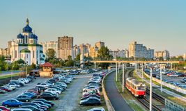 Cathedral of the Holy Trinity and a light rail tram in Troieshchyna - Kiev, Ukraine. The Cathedral of the Holy Trinity, a car parking and a light rail tram in royalty free stock images