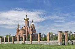 Cathedral of the Holy Virgin in the town of Minera. Cathedral with gilded domes against the blue sky behind the iron fence stock image