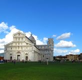 Cathedral and leaning tower on background of blue sky with clouds royalty free stock images