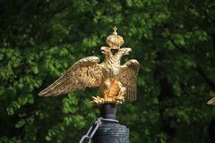 Gilded double headed imperial eagle of the Transfiguration Cathedral wall on the background of green foliage close up stock images