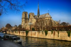 Facade of Notre Dame cathedral in Paris next to the Seine River. Royalty Free Stock Images