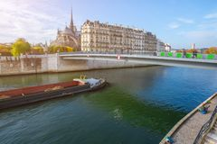 Cathedral of Notre Dame de Paris at autumn afternoon. Embankment of the Seine. Barge carrying a cargo Tourists and natives a walk stock photography