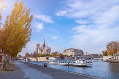 Cathedral of Notre Dame de Paris at sunny autumn afternoon. Embankment of the Seine. Boat on scenic route. Tourists a walk and royalty free stock photos