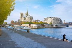Cathedral of Notre Dame de Paris at sunny autumn afternoon. Embankment of the Seine. Boat on scenic route. Tourists a walk and royalty free stock photo