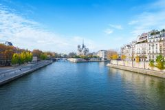 Cathedral of Notre Dame de Paris sunny autumn afternoon. Embankment of the Seine River. The natives and tourists take a walk and royalty free stock images
