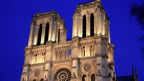 Cathedral of Notre Dame in Paris. Facade of Notre Dame cathedral in Paris next to the Seine River at night stock video footage