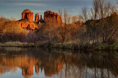 Cathedral Rock in Sedona, Arizona. Setting sun turns Sedona's normally red rocks into a dark orange. Shot at Red Rock Crossing Stock Photography