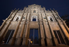 Cathedral with Ruins of St Paul illuminated at night. Boy jumps in front of the Cathedral of St Paul ruins in Macau, China at night Royalty Free Stock Photo