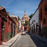 Cathedral of San Miguel de Allende in Mexico Behind Colorful Mexican Buildings and a Vintage Car Royalty Free Stock Photo
