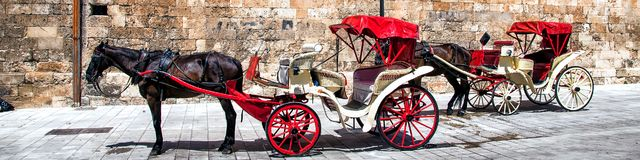 The Cathedral of Santa Maria of Palma de Majorca, Spain. Majorca, Spain. A horse carriage near an old building wall of The Cathedral of Santa Maria of Palma de Royalty Free Stock Photos