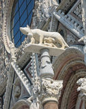 Cathedral of Siena, Italy. Exterior of the Cathedral of Siena featuring the statue of the she-wolf of Siena with Romulus and Ramus Royalty Free Stock Images