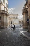 Cathedral in Lecce with couple cycling - Salento – Italy. Cathedral square in Lecce - Salento – Italy Stock Image