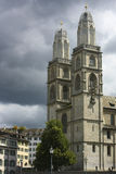 A sunlit cathedral in Zurich, Switzerland in front of menacing storm clouds. Stock Photo