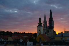 Cathedral before Sunrise. View of Rooftops and Bell Towers of Cathedral and St. Mary Church in Zagreb against color cloudy sky at the dawn Stock Image