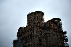 Cathedral under construction. A cathedral under construction, cloudy rainy weather, surrounded by wooden scaffolding Stock Photo