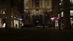 Cathedral in Vienna Close Up. Christian Cathedral in Vienna taken by night with many lights, traffic and people walking in front of it stock footage