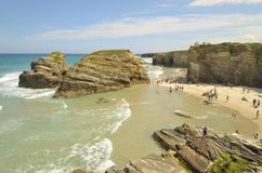 Cathedrals beach. Lugo, Spain - August 5, 2013: Many tourists visit the Cathedrals beach at low tide. During this time, the caves of the cliffs are visible Royalty Free Stock Photography