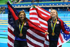 Catherine Meili L e Lilly King do Estados Unidos comemoram após o final dos bruços do ` s 100m das mulheres do Rio 2016 Olympics imagem de stock royalty free