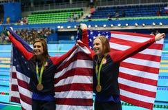 Catherine Meili L en Lilly King van de Verenigde Staten vieren na Def. van de Vrouwen` s 100m Schoolslag van Rio 2016 Olympics stock foto