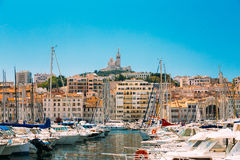 Catholic Basilica of Our Lady of the Guard or Notre Dame De La G. Arde church at hill in Marseille, France. White Yachts Are Moored At City Pier, Jetty, Port royalty free stock images