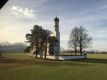 Catholic Bavarian Church in the countryside. Picture taken in 2015. View of Bavarian Alps in the background. Bavarian Church with Domed Bell Tower. Picture taken Royalty Free Stock Images