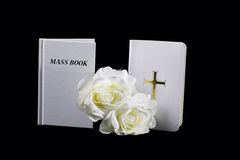 Catholic Books. A white Bible and Mass Book on a black background with flowers royalty free stock photography