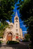 Catholic Cathedral Basilica with a high spire. Landscape against the blue sky. In the foreground are the crowns of trees royalty free stock photos